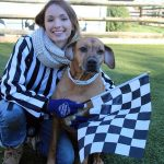 woman dressed up a racing referee with a dog